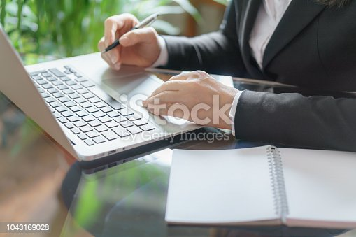 663458084 istock photo Business woman working with laptop, copybook and pen. Business and law concept. Selective focus 1043169028