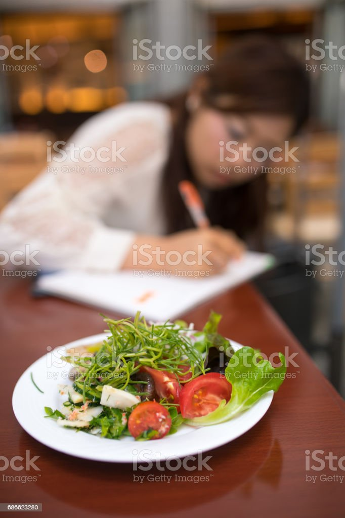 Business woman writing message on paper in cafe, salad is served royalty-free stock photo