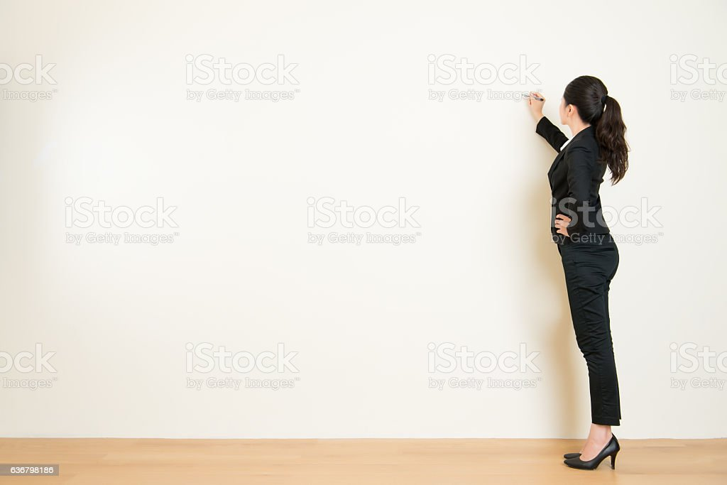 Business woman writing something on white wall stock photo