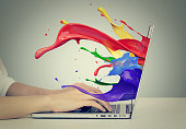 istock business woman's hands on keyboard using laptop with colorful splashes, liquid effect out of monitor screen computer display 671826820