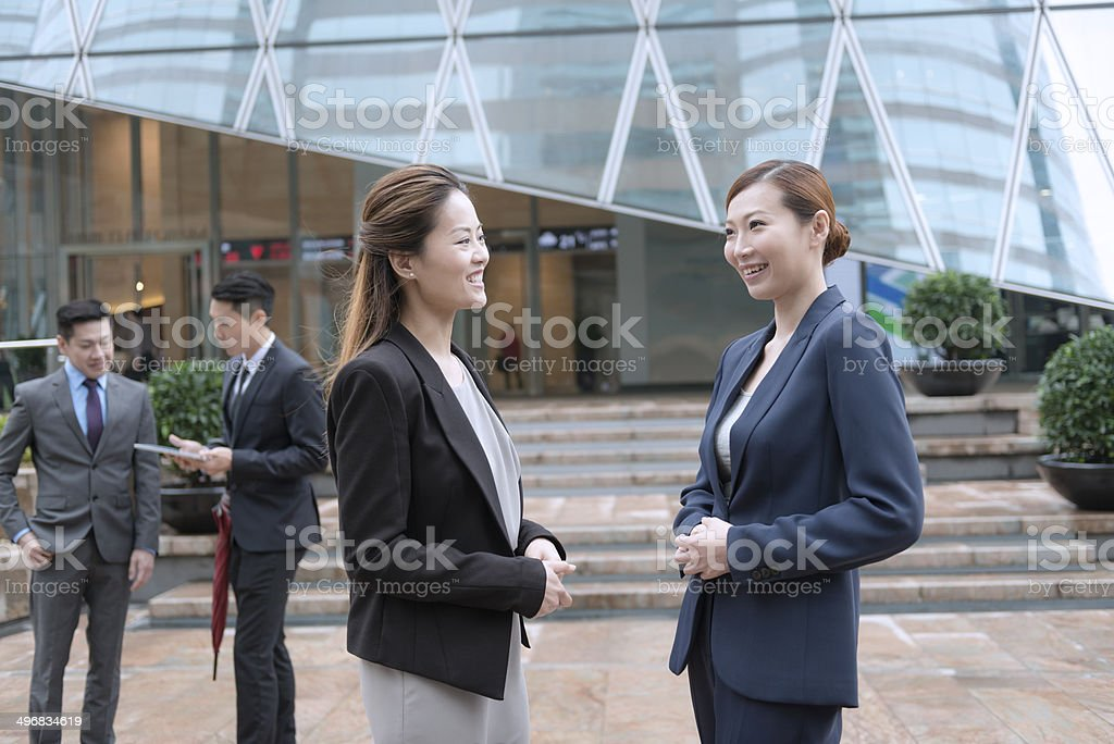 Business Women and Coleeges with Mobile Devices, Hong Kong, Asia stock photo