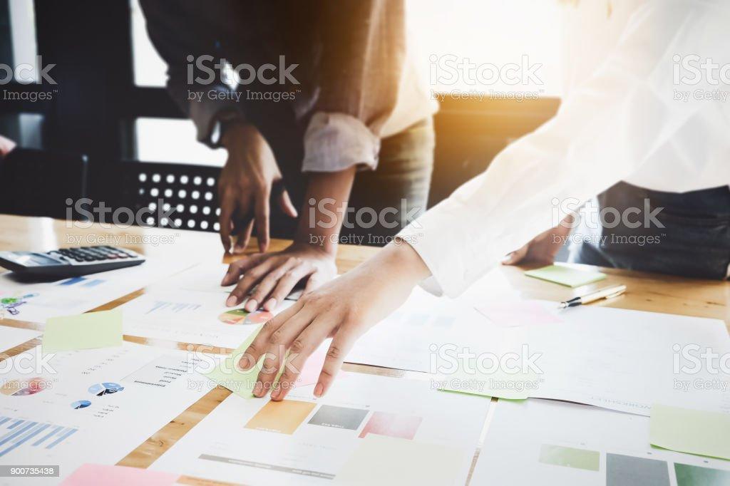 Parceiros e mulheres de negócios estão a analisar o plano de marketing da empresa com a calculadora na mesa de madeira no local de trabalho. - foto de acervo