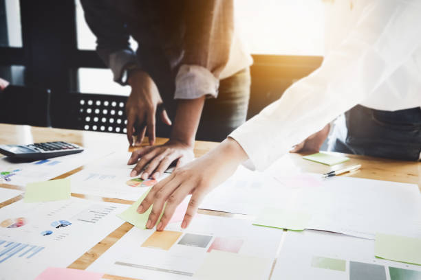 mujeres de negocios y socios están analizando el plan de marketing de la empresa con la calculadora en el escritorio de madera en el lugar de trabajo. - trabajo de oficina fotografías e imágenes de stock