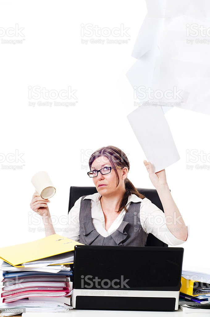 Business women at desk throwing paper up in air royalty-free stock photo