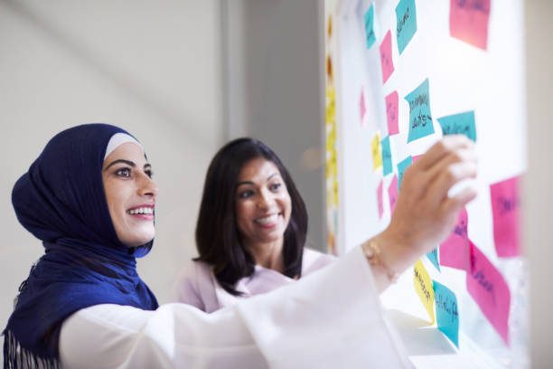 Business women brainstorming with sticky notes stock photo