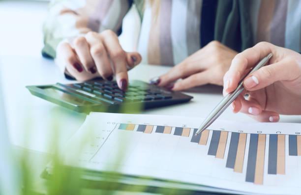 Geschäftsfrauen diskutieren die Diagramme und Graphen, die die Ergebnisse ihrer erfolgreichen Teamarbeit zeigen. Die Kollegen prüfen die Ergebnisse des Quartalsberichts mit einem Rechner. – Foto