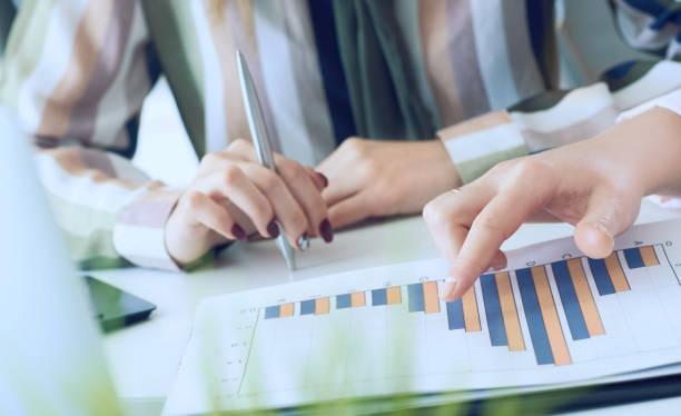 Geschäftsfrauen diskutieren die Diagramme und Grafiken, die die Ergebnisse ihrer erfolgreichen Teamarbeit zeigen. Hände nur über den Tisch. – Foto