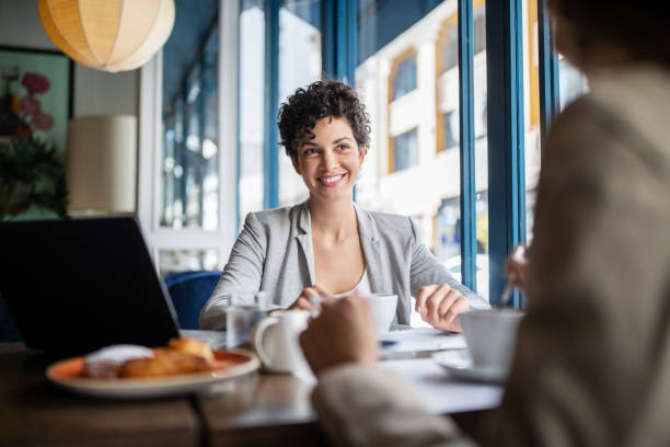 Business women having meeting at cafe stock photo