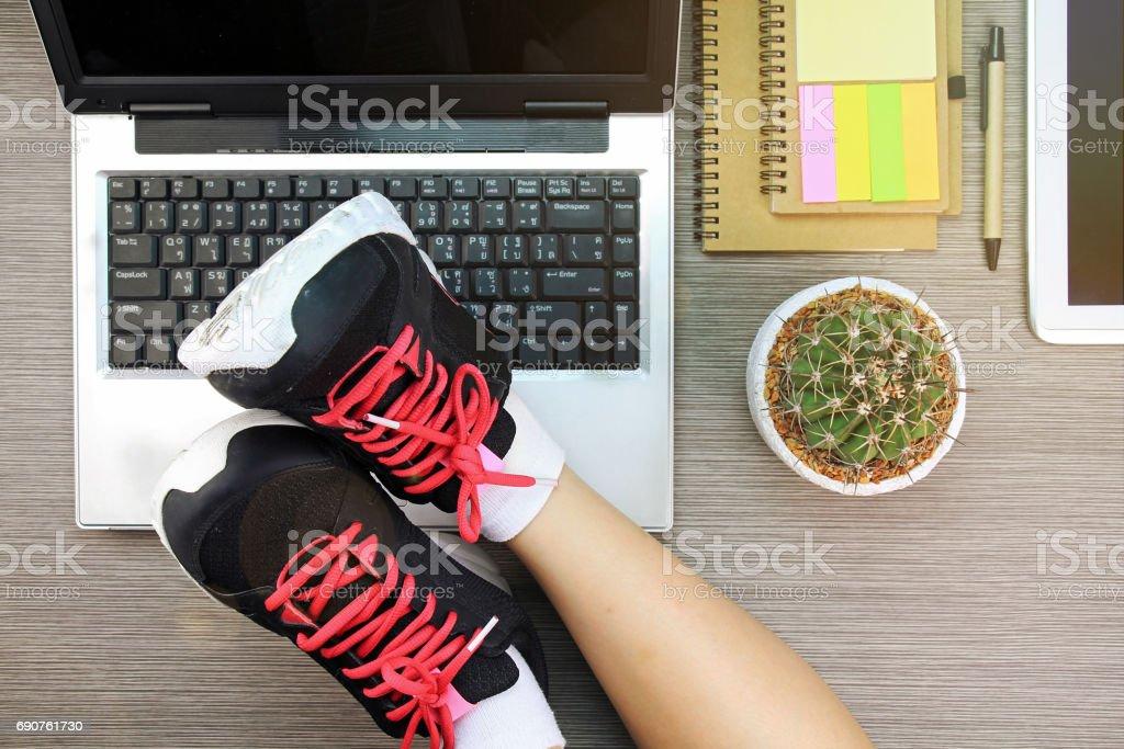 Business-Frauen legen ihre Beine in Sportschuhen über den Laptop, balance Leben und Werk Konzept. – Foto