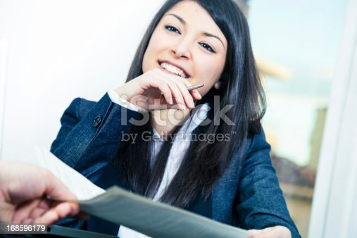 155279487 istock photo Business women receiving contracts 168596179