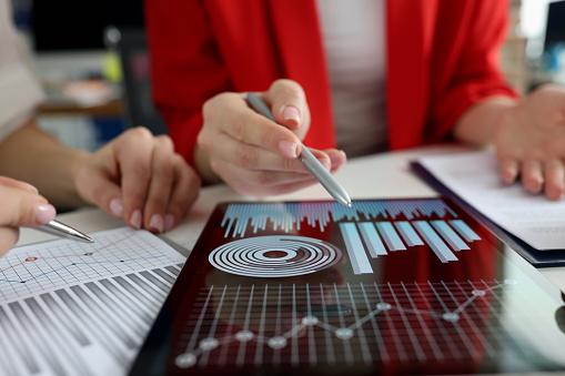 Business women studying charts and diagrams on digital tablet closeup. Business meetings concept