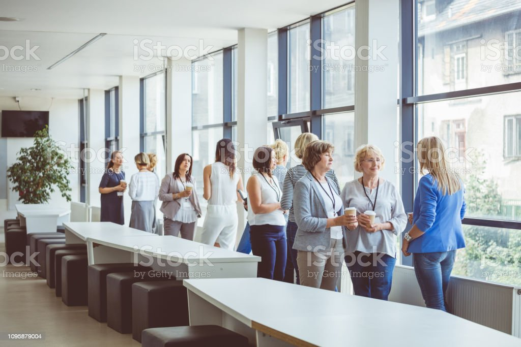 Business women talking in office lobby during break Group of business women talking in office lobby during break. Women during a break in seminar. Adult Stock Photo