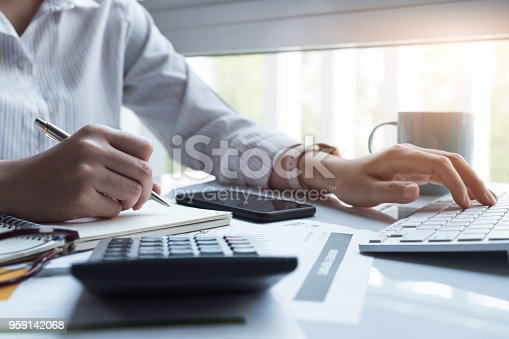 istock Business women using computer and calculator during note some data on notepad for calculate financial at home office 959142068