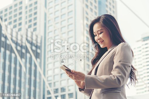 istock Business women using social network connection modern city background.  Technology and Business Concept 1130294457