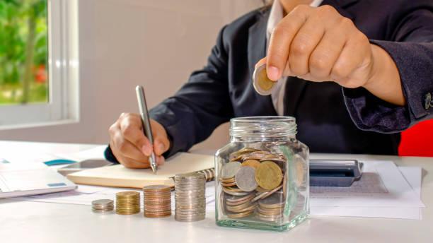 mujeres de negocios que están poniendo monedas en un frasco de dinero, incluyendo un cuaderno en un escritorio de madera para el trabajo, ideas para ahorrar dinero y administrar cuentas. - gerente de cuentas fotografías e imágenes de stock