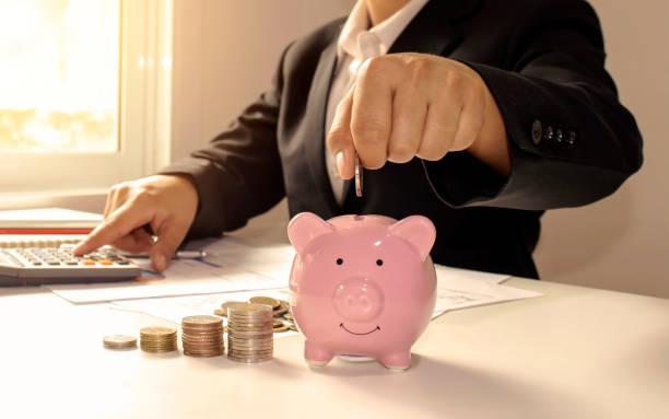 mujeres de negocios que tienen monedas en una alcancía de cerca, incluyendo presionar una calculadora, ahorrar ideas y ahorrar dinero para los gastos de negocios. - gerente de cuentas fotografías e imágenes de stock