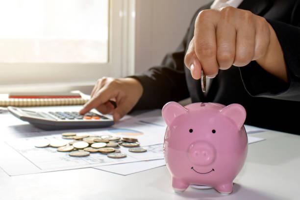 mujeres de negocios que tienen monedas en una alcancía de cerca, incluyendo presionar una calculadora para ideas de ahorro de dinero. - gerente de cuentas fotografías e imágenes de stock