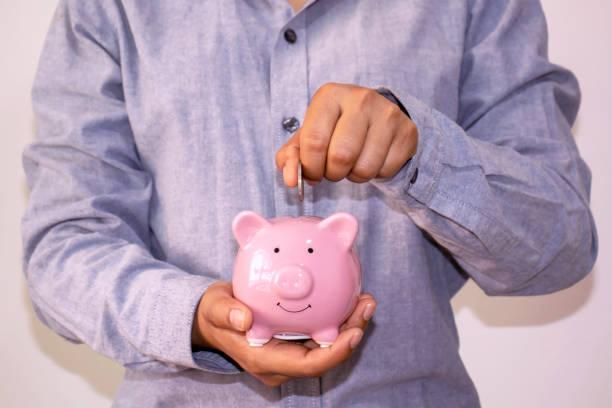 mujeres de negocios que ponen monedas en una alcancía, el concepto de ahorrar dinero y ahorrar dinero para el futuro. - gerente de cuentas fotografías e imágenes de stock