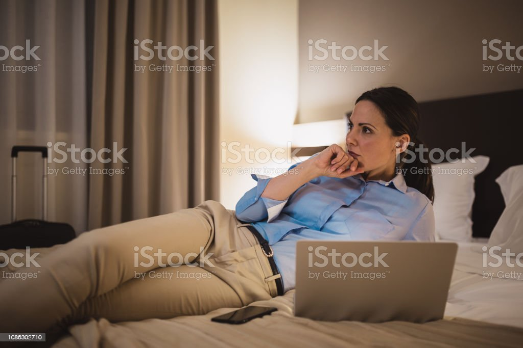 Young women working late in hotel room, using laptop, after business...