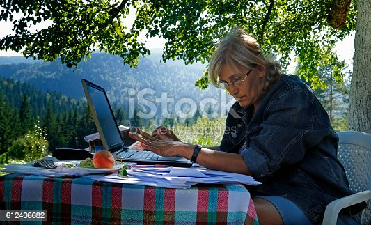 Business women working outdoors on a laptop.