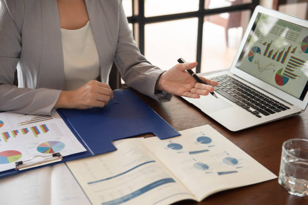 Business women working Business women reviewing data in financial statement with coworker analyzing market data research for new business startup. financial report stock pictures, royalty-free photos & images