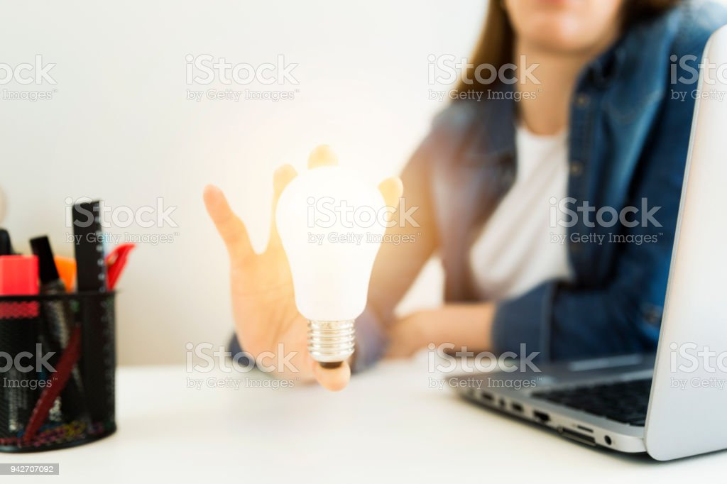 Business women's, designer's hand holding light bulb, concept of new ideas with innovation and creativity. stock photo