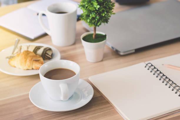 Geschäft am Arbeitsplatz und Business-Objekte wie Laptop, Notizbuch, Taschenrechner, Kugelschreiber, eine Tasse Kaffee, Blumen, Brot, Bild Balkendiagramm etc.. Fokus Tasse Kaffee – Foto