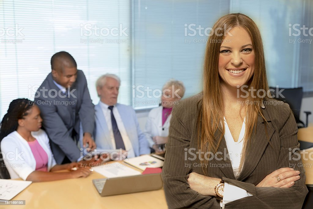 Business: Young adult businesswoman and her team. royalty-free stock photo