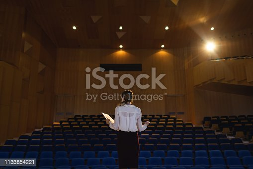 1133973551 istock photo Businessawoman practicing and learning script while standing in the auditorium 1133854221