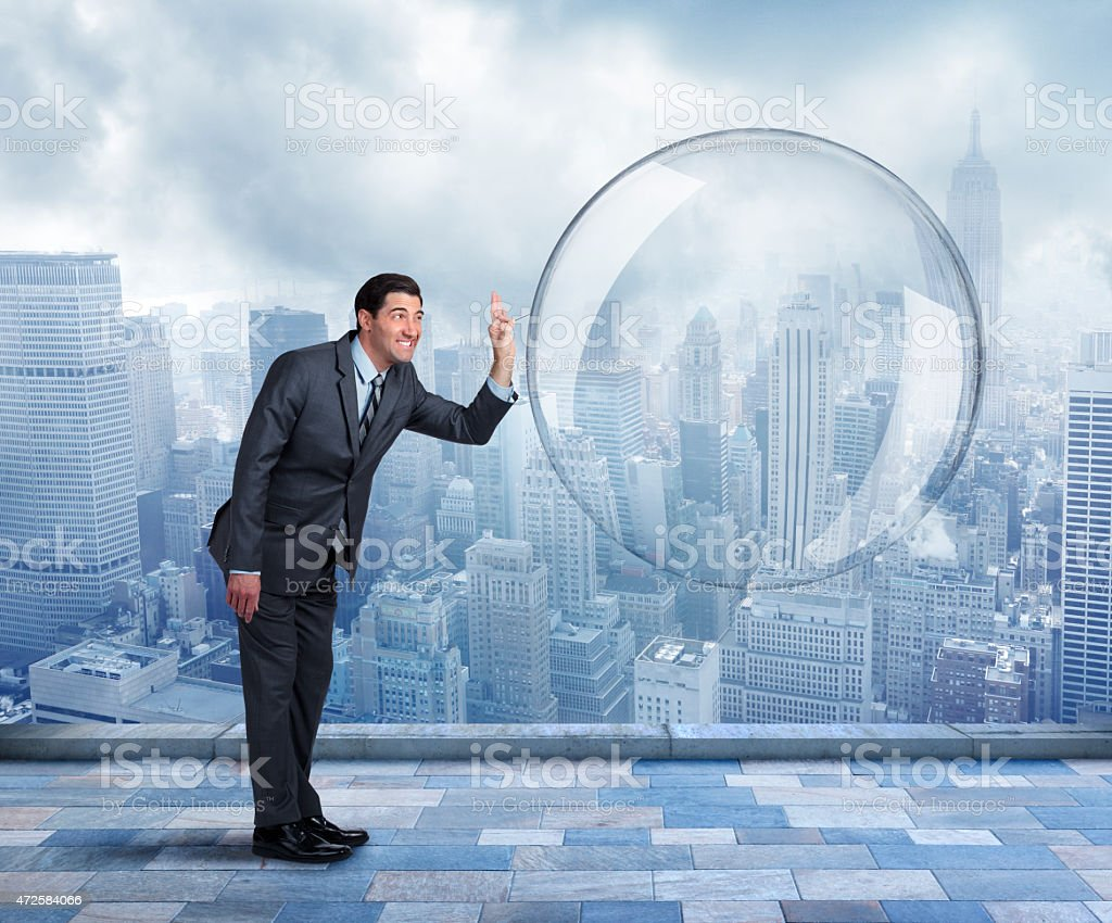 Businessman about to pop a large bubble stock photo
