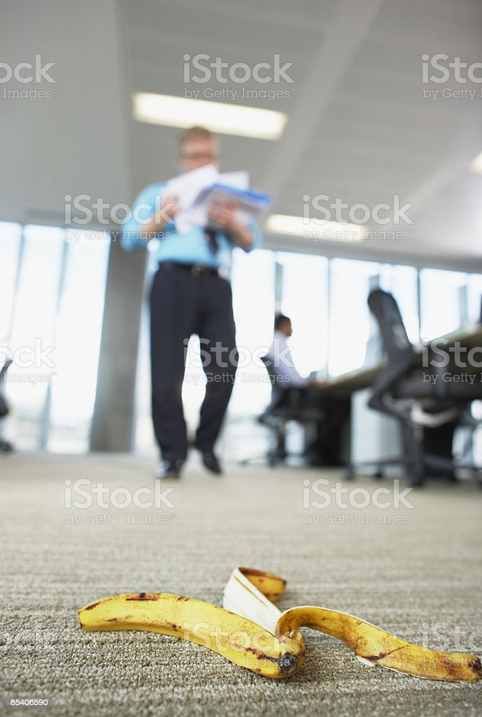 Businessman about to step on banana peel stock photo
