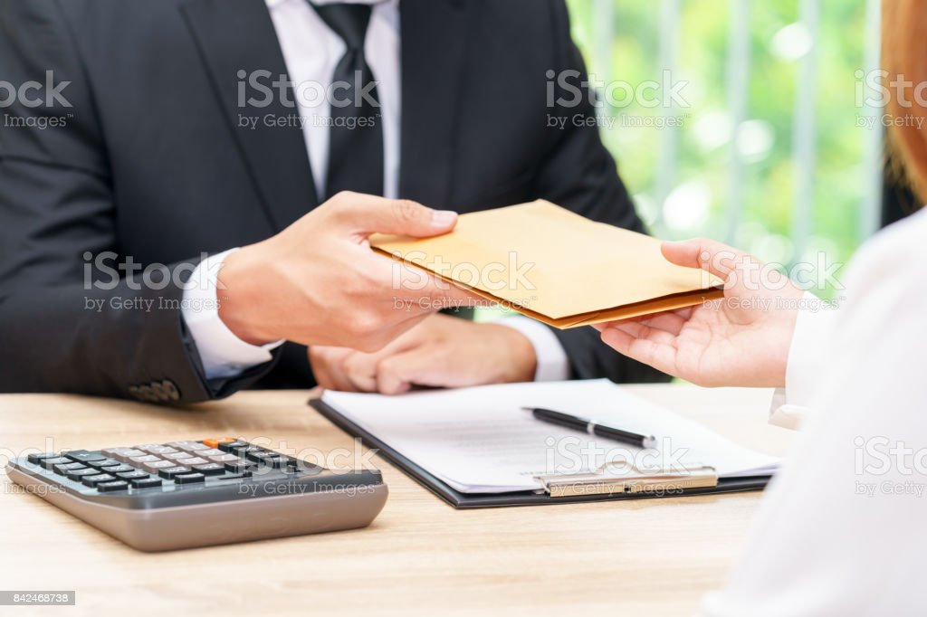 Businessman accepting money in envelope offered by a woman - corruption concepts. stock photo