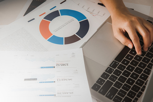 1044507110 istock photo Businessman accountant or financial expert analyze business report graph and finance chart at corporate office. Concept of finance economy, banking business and stock market research. 1252997112