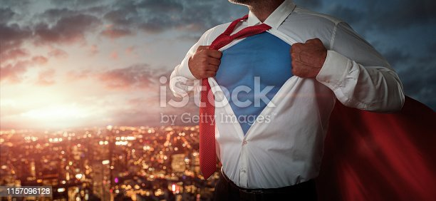 Young businessman acting like a superhero and tearing his shirt off over the city at the sunset with copy space