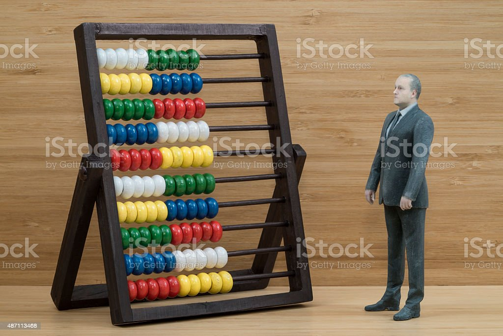 Businessman Action Figure with Abacus Businessman action figure with abacus on wooden shelf. 2015 Stock Photo