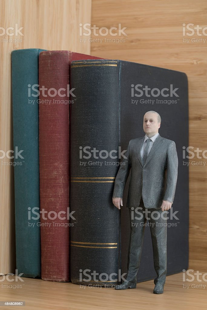 Businessman Action Figure with Old Books royalty-free stock photo