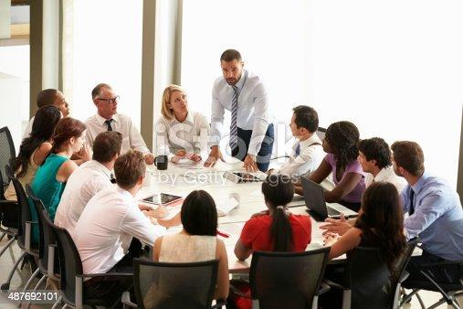 istock Businessman addressing collegues around table 487692101
