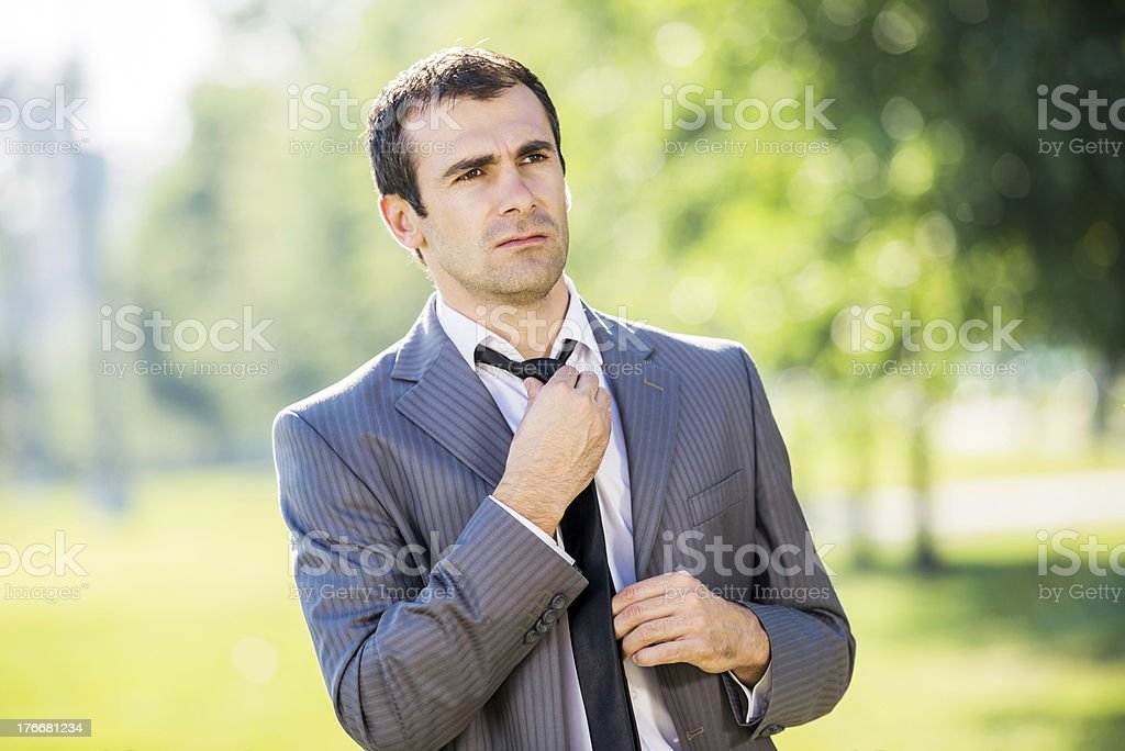 Businessman adjusting his bow tie outdoors. royalty-free stock photo