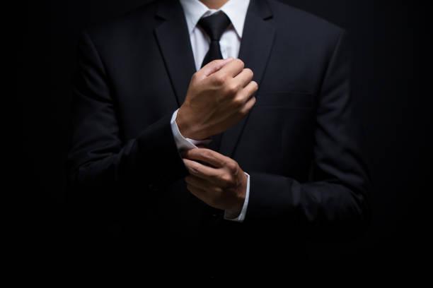 homme d'affaires ajuster ses boutons de manchette - cravate photos et images de collection