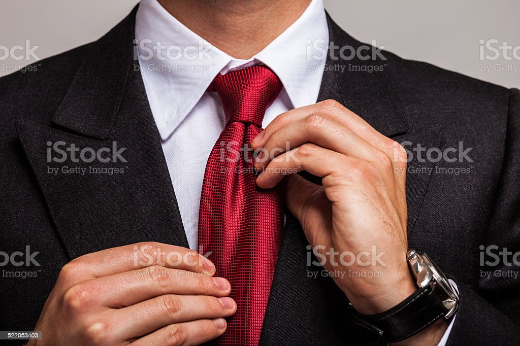Businessman adjusting his necktie stock photo
