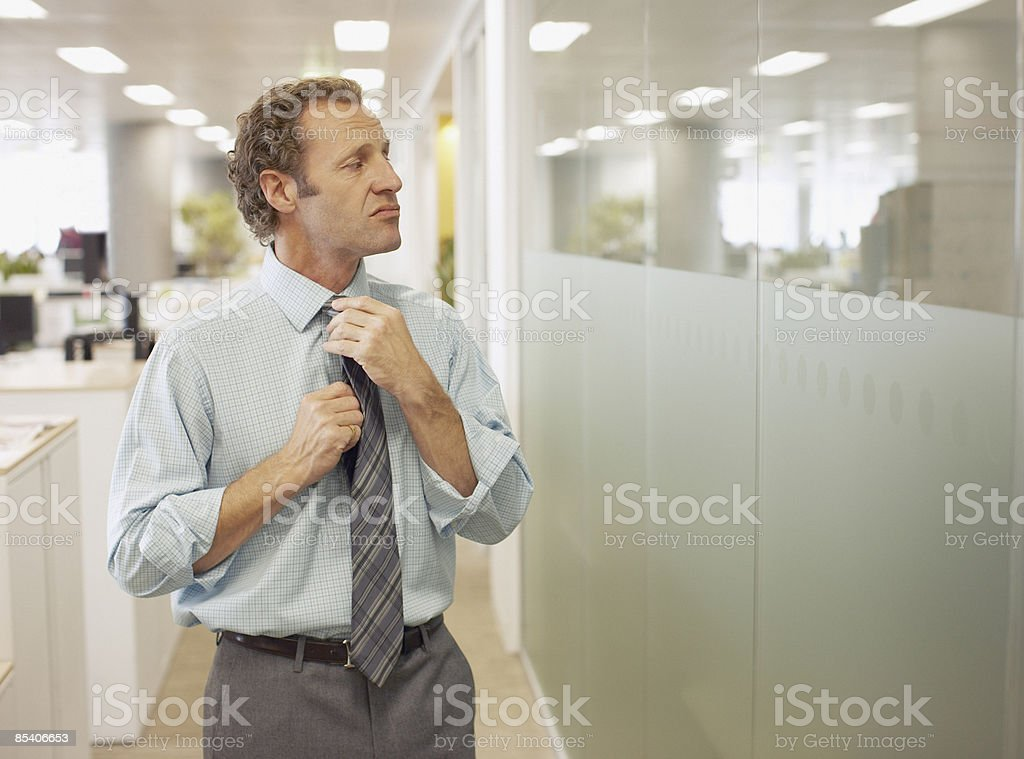 Businessman adjusting tie in office stock photo