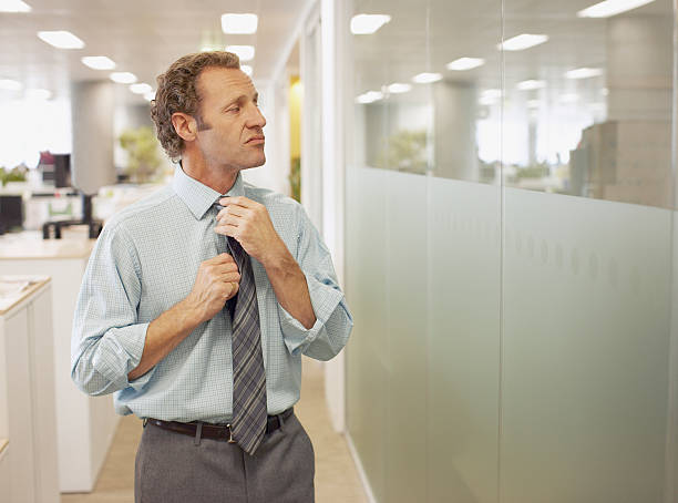 Businessman adjusting tie in office stock photo