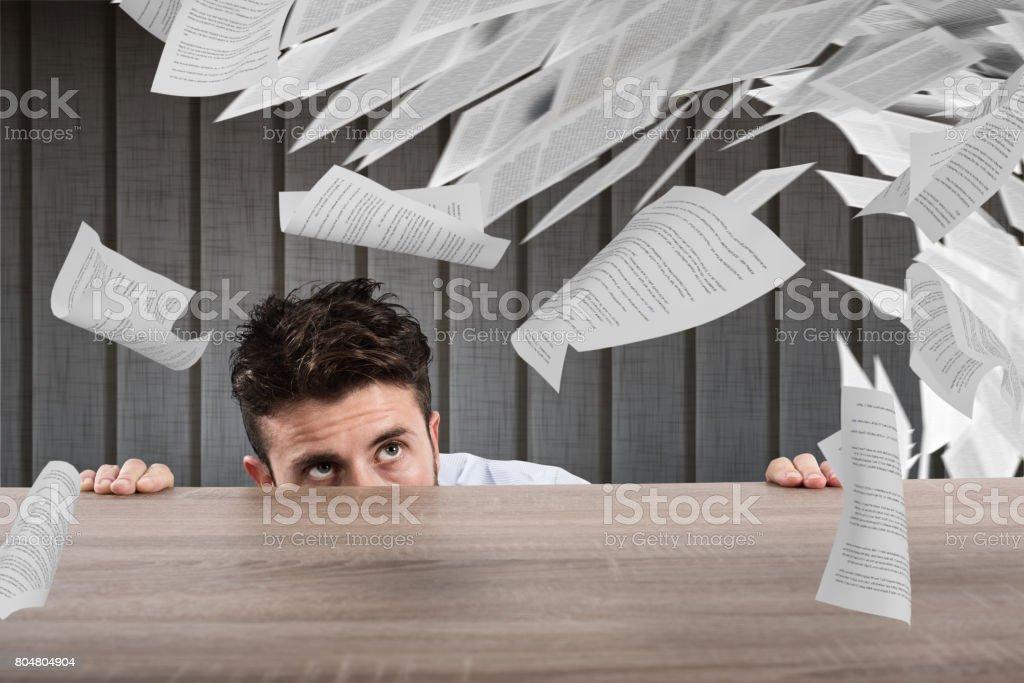 Businessman afraid under the desk. concept of overwork stock photo