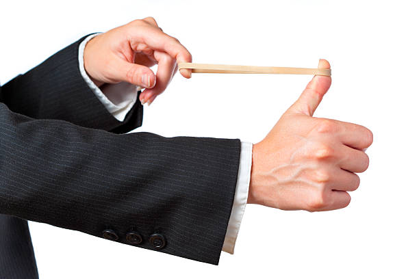 A businessman aiming a rubber band on a white background stock photo