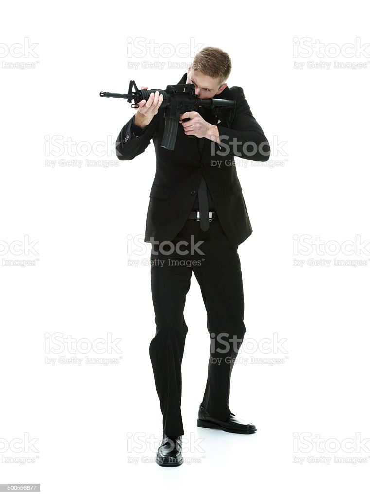 Businessman aiming with machine gun stock photo