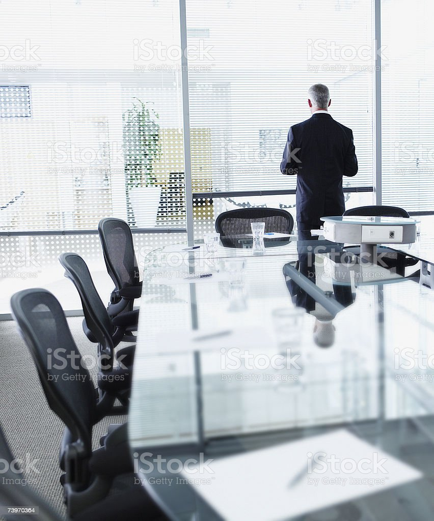 Businessman alone in a boardroom facing window royalty-free stock photo