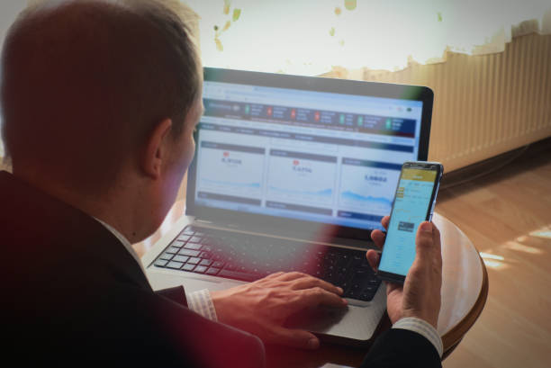Businessman analysing stock market exchanges from phone and laptop at home stock photo