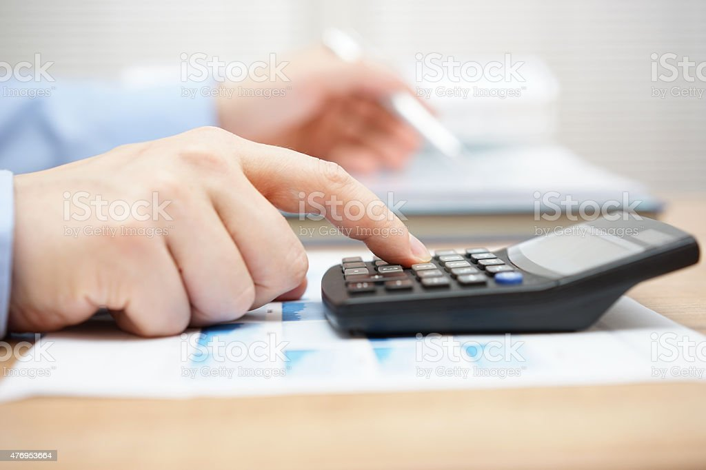 Businessman analyzing business data and using calculator stock photo