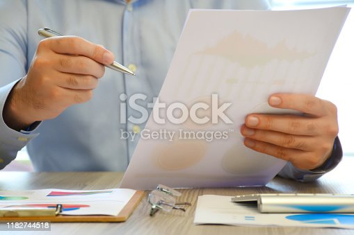 1068752548 istock photo A businessman analyzing business graphs on the office desk 1182744518