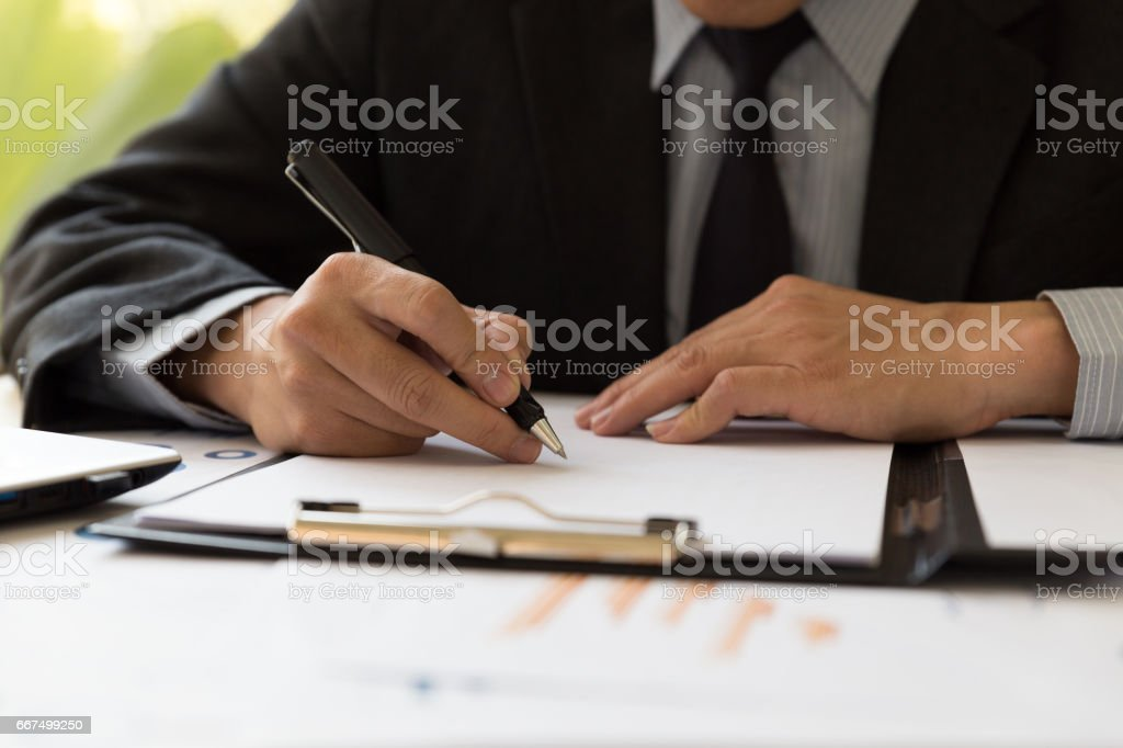 Businessman analyzing charts and graphs and taking notes. foto stock royalty-free